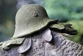Grabstein mit Soldatenhelm am Volkstrauertag.