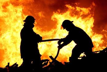 Silhouette zweier Feuerwehrleute, die gegen ein tobendes Feuer mit riesigen Flammen kämpfen.